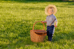 Toddler child outdoors. One year old baby boy wearing straw hat holding picnic basket Royalty Free Stock Photos