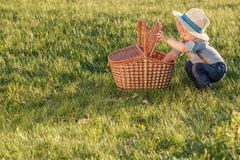 Toddler child outdoors. One year old baby boy wearing straw hat looking in picnic basket. Portrait of toddler child outdoors. Rural scene with one year old baby Royalty Free Stock Image