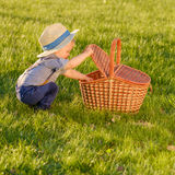 Toddler child outdoors. One year old baby boy wearing straw hat looking in picnic basket stock photos