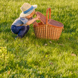 Toddler child outdoors. One year old baby boy wearing straw hat looking in picnic basket Royalty Free Stock Photo