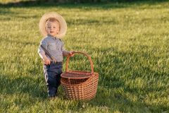 Toddler child outdoors. One year old baby boy wearing straw hat with picnic basket Royalty Free Stock Photos