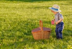 Toddler child outdoors. One year old baby boy wearing straw hat with picnic basket Royalty Free Stock Image
