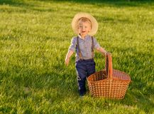 Toddler child outdoors. One year old baby boy wearing straw hat with picnic basket. Portrait of toddler child outdoors. Rural scene with one year old baby boy stock images