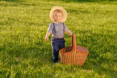 Toddler child outdoors. One year old baby boy wearing straw hat with picnic basket Royalty Free Stock Photo