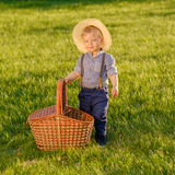 Toddler child outdoors. One year old baby boy wearing straw hat with picnic basket Stock Photos