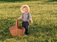 Toddler child outdoors. One year old baby boy wearing straw hat with picnic basket Royalty Free Stock Images