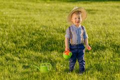 Toddler child outdoors. One year old baby boy wearing straw hat using watering can royalty free stock image