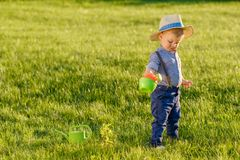 Toddler child outdoors. One year old baby boy wearing straw hat using watering can. Portrait of toddler child outdoors. Rural scene with one year old baby boy royalty free stock image