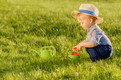 Toddler child outdoors. One year old baby boy wearing straw hat using watering can royalty free stock photos