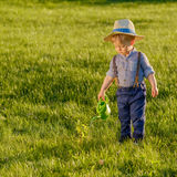Toddler child outdoors. One year old baby boy wearing straw hat using watering can. Portrait of toddler child outdoors. Rural scene with one year old baby boy royalty free stock photos
