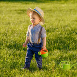 Toddler child outdoors. One year old baby boy wearing straw hat using watering can. Portrait of toddler child outdoors. Rural scene with one year old baby boy royalty free stock photo