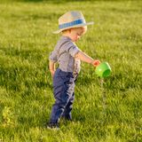 Toddler child outdoors. One year old baby boy wearing straw hat using watering can. Portrait of toddler child outdoors. Rural scene with one year old baby boy royalty free stock images