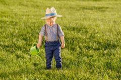 Toddler child outdoors. One year old baby boy wearing straw hat using watering can. Portrait of toddler child outdoors. Rural scene with one year old baby boy royalty free stock photography