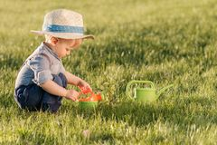 Toddler child outdoors. One year old baby boy wearing straw hat using watering can. Portrait of toddler child outdoors. Rural scene with one year old baby boy stock photography