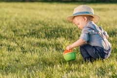 Toddler child outdoors. One year old baby boy wearing straw hat using watering can. Portrait of toddler child outdoors. Rural scene with one year old baby boy stock photo