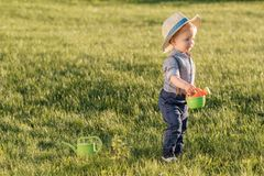 Toddler child outdoors. One year old baby boy wearing straw hat using watering can. Portrait of toddler child outdoors. Rural scene with one year old baby boy stock photos