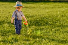 Toddler child outdoors. One year old baby boy wearing straw hat using watering can. Portrait of toddler child outdoors. Rural scene with one year old baby boy stock image