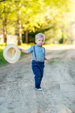 Toddler child outdoors. Rural scene with one year old baby boy with straw hat Stock Image