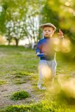 Toddler child outdoors. Rural scene with one year old baby boy wearing flat cap Stock Image