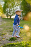 Toddler child outdoors. Rural scene with one year old baby boy wearing flat cap Royalty Free Stock Image