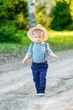 Toddler child outdoors. Rural scene with one year old baby boy wearing straw hat Royalty Free Stock Photography