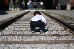 Toddler child playing on railroad. A boy plays on the railroad tracks Royalty Free Stock Images