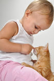 Toddler child plays with a cat Stock Photos