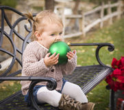 Toddler Child Sitting on Bench with Christmas Ornament Outside Royalty Free Stock Image