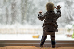 Toddler child standing in front of a big window leaning against Stock Photos