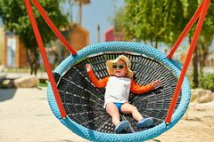 Toddler child swinging on beach. Portrait of toddler child swinging on beach. Kid playing outside Royalty Free Stock Photos