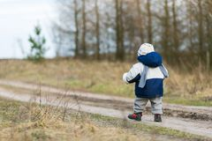 Toddler child walking by rural sandy road Stock Photography