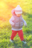 Toddler child in warm vest jacket outdoors. Baby boy at park during sunset. Stock Images