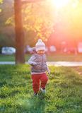 Toddler child in warm vest jacket outdoors. Baby boy at park during sunset. Royalty Free Stock Photos