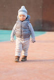 Toddler child in warm vest jacket outdoors. Baby boy at playground during sunset. Stock Photography