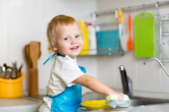 Toddler child washing dishes in kitchen. Little Stock Photo