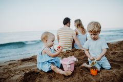 Toddler children with parents playing on sand beach on summer holiday. stock photo