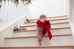 Toddler With Christmas Bow On Stairs In Pajamas Royalty Free Stock Photography