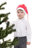 Toddler in christmas hat decorating new year tree Stock Photos