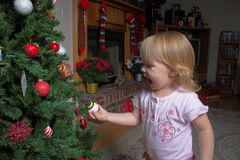 Toddler and Christmas tree. Closeup of happy toddler touching decoration of traditional Christmas tree Royalty Free Stock Photography