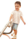 Toddler is cleaning room with vacuum cleaner Stock Photo