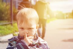 Toddler click on his nose by finger. Sad offended boy dont`t want to play outdoor stock images