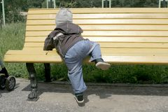 Toddler climbing on bench Stock Photography