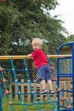 Toddler climbing on frame. Little toddler on climbing frame in the local park Royalty Free Stock Photography