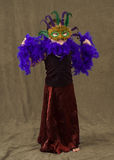 Toddler Costume. A female toddler wearing a pretty dress and a feather mask along with a feather boa Stock Image