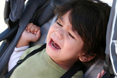Toddler crying in stroller royalty free stock images