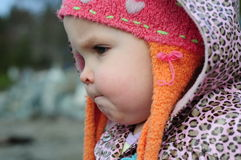 Toddler with the cute face. Toddler outside with a colourful hat and coat, with a fun expression on her face Royalty Free Stock Photography