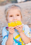 Toddler cute girl eating boiled corn Royalty Free Stock Images