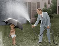 Toddler and dad playing with hose in yard Stock Photos