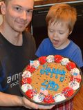Toddler and Daddy with giant Independence Day Cookie. Toddler is WOWed by a giant Independence Day - Fourth of July - cookie with flags, frosting, and red white Royalty Free Stock Images