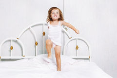 Toddler dancing in bed Stock Photo